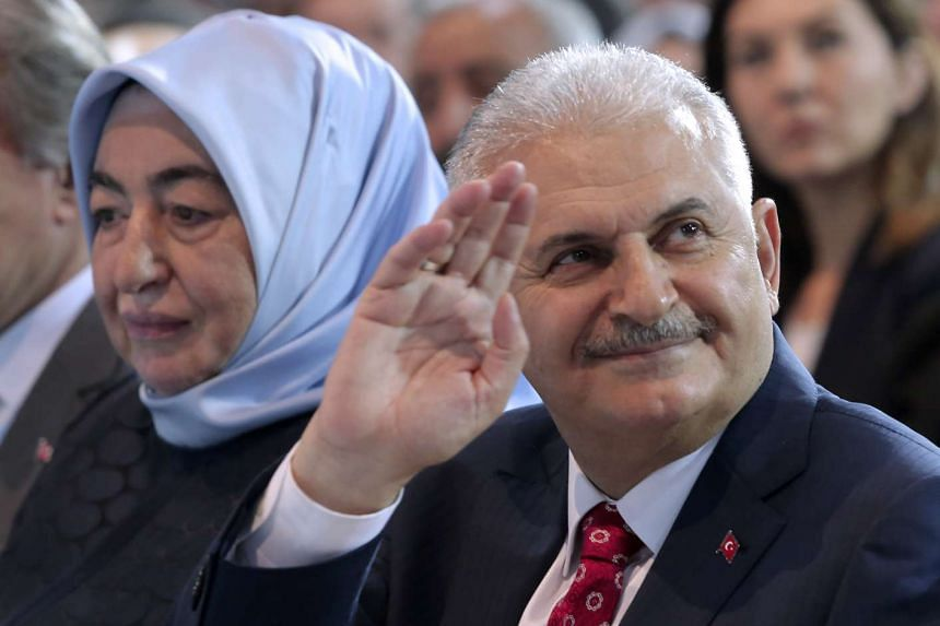 Egypt's Transport Minister Binali Yildirim (right) flanked by his wife Semiha Yildirim, greets supporters as he attends the second extraordinary congress of the AK Party in Ankara, on May 22, 2016.