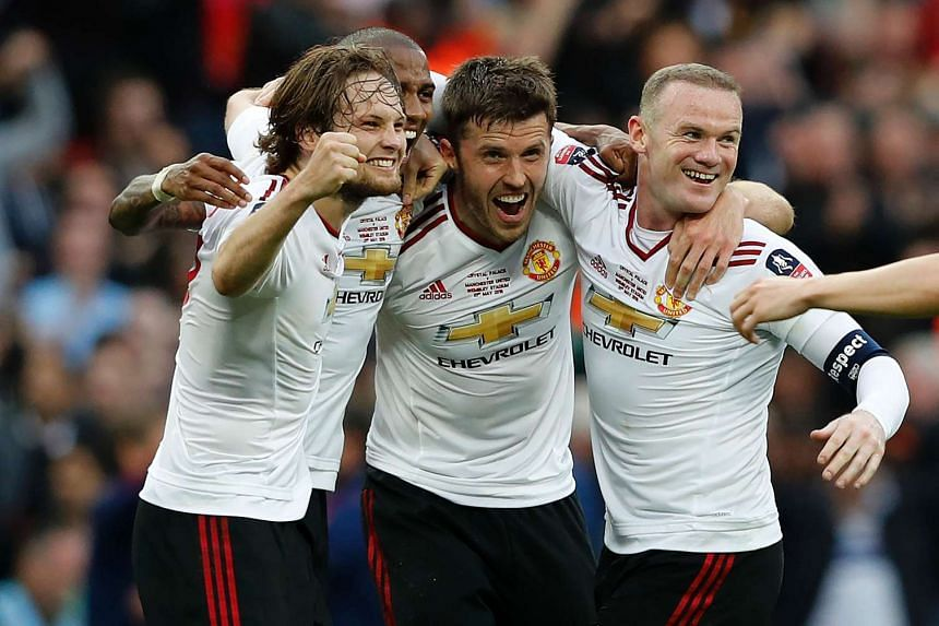 United players (from left) Daley Blind, Ashley Young, Michael Carrick and Wayne Rooney celebrate on the final whistle.