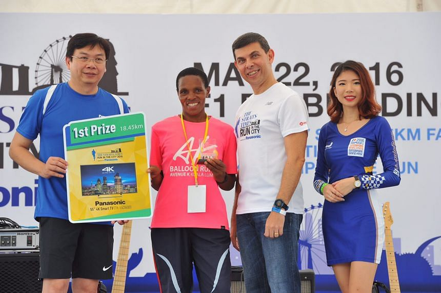 Margaret Njuguna (centre) of Kenya accepts the first prize award in The Straits Times Run in the City Women's 18.45km category.