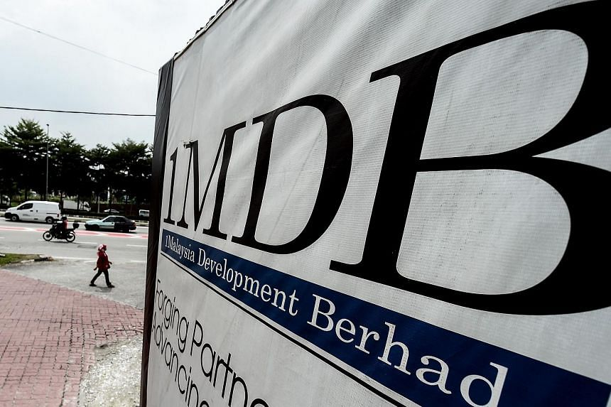 A woman walking past a billboard with the 1MDB logo at the funds flagship Tun Razak Exchange construction site in Kuala Lumpur.