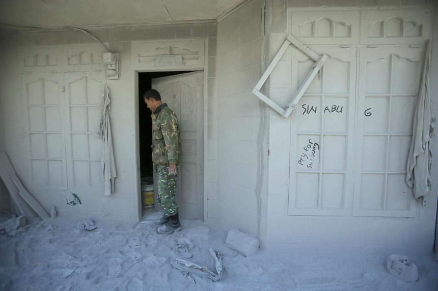An Indonesian soldier inspects an abandoned house covered by volcanic ash following Mount Sinabung's eruption, on May 23, 2016.