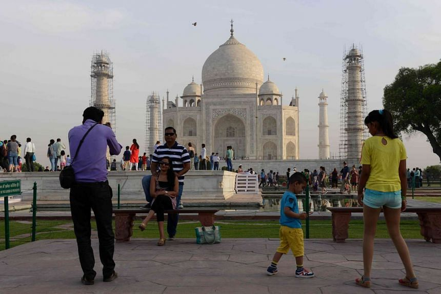 A photographer takes a picture of a couple as they pose in front of the Taj Mahal in Agra, on April 16, 2016.