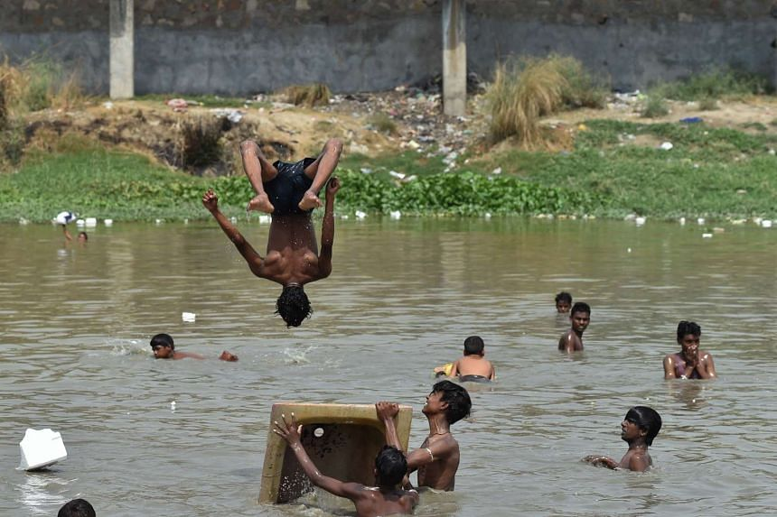 Indian children take a dip in a pond to escape the afternoon heat in New Delhi on May 22, 2016.