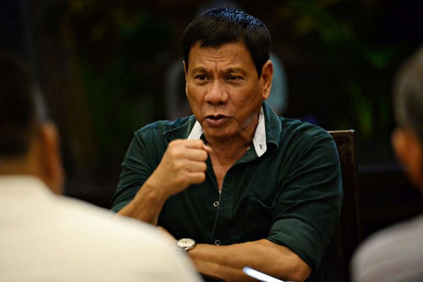 Philippines' president-elect Rodrigo Duterte (centre) speaking to military and police officials at a hotel in Davao City, on May 15, 2016.