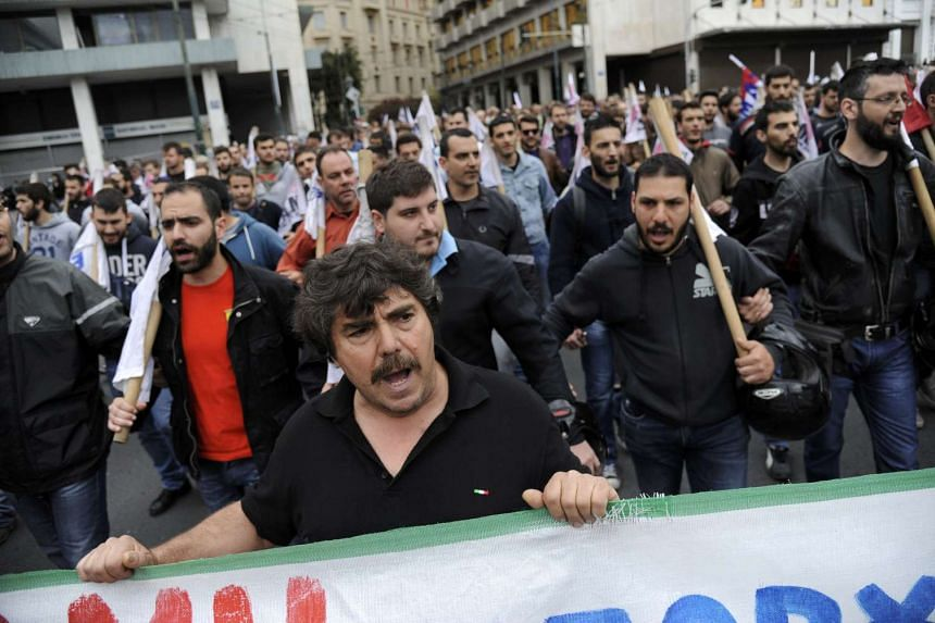 Protesters of the communist-affiliated PAME union shout slogans during a demonstration against a new package of tax hikes and reforms in Athens, Greece, on May 22, 2016.