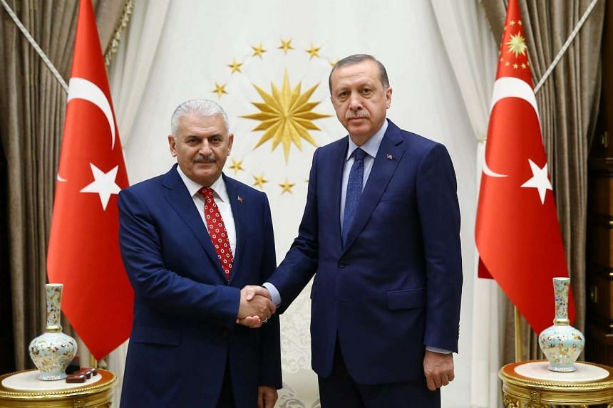 A handout picture provided by Turkish President Press office shows, Turkish President Recep Tayyip Erdogan (right) shake hands with Turkish Transportation Prime Minister Binali yildirim (left), in Ankara, Turkey, on May 22, 2016.