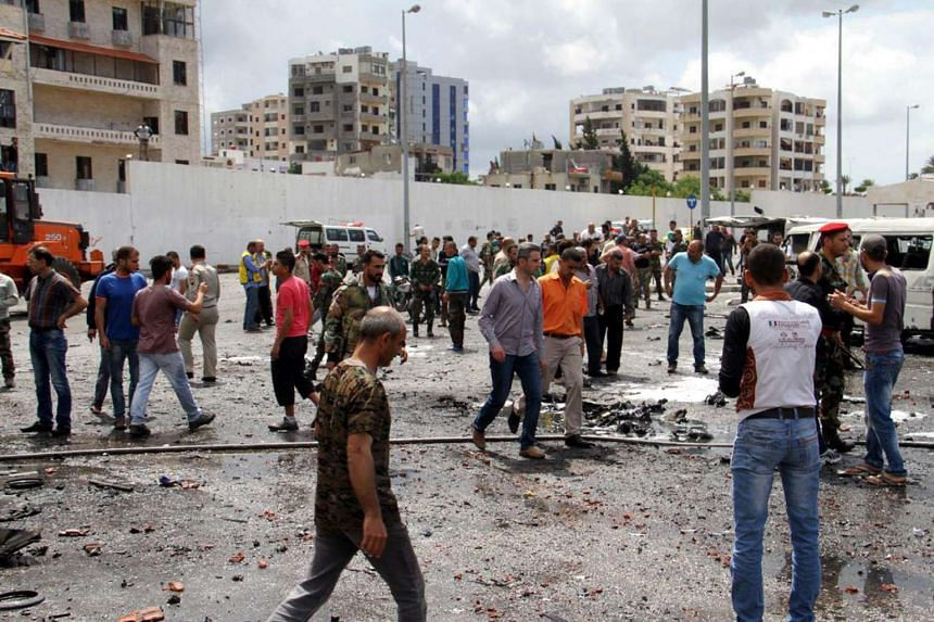 People inspecting the bombing site at a bus station in the coastal city of Tartus, Syria, on May 23, 2016.