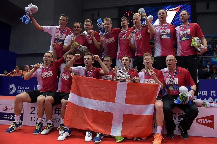 Hans-Kristian Vittinghus (left) pointing to the Danish flag on his shirt in celebration following his 21-15, 21-7 victory over Indonesia's Ihsan Maulana Mustofa to seal Denmark's first Thomas Cup triumph. The Denmark team (above) celebrating with the