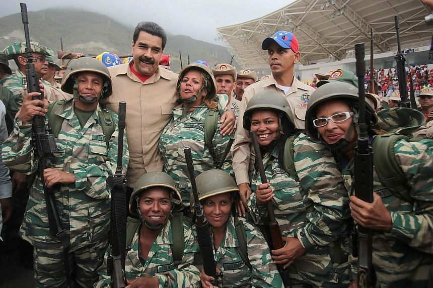 Venezuela's President Nicolas Maduro (back row second from left) posing for a photo with militia members during a military parade in La Guaira, Venezuela, on Saturday. The country held what it called its biggest military exercises on Friday and Satur