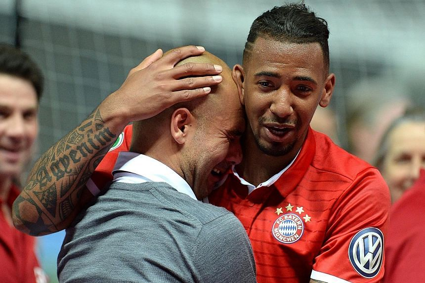 Bayern Munich's outgoing coach Pep Guardiola is comforted by Jerome Boateng after being overwhelmed with emotion following the German Cup final against Dortmund. The Bavarians overcame their fierce rivals to lift the cup, scant reward for missing out