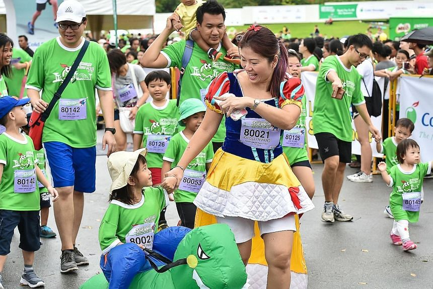 """Three-year-old Merrily Tan """"rode"""" her way on an inflated dinosaur to win the Fancy Dress Family Fun category at the Cold Storage Kids Run yesterday with her mother, Joycelyn Pang, 39, who came dressed as Snow White. The mother-daughter pair were amon"""
