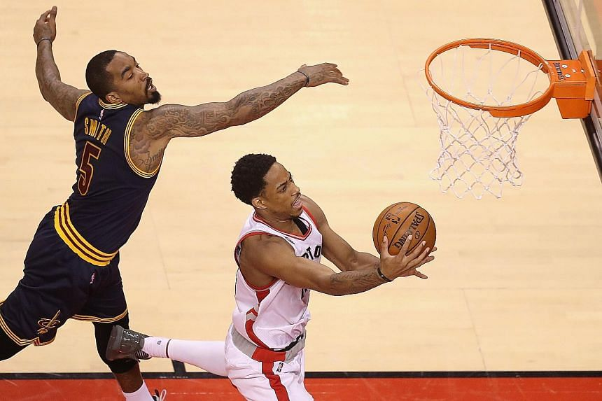 Toronto's DeMar DeRozan, who top-scored with 32 points, getting in a shot despite the close attention of Cleveland's J.R. Smith in Game 3 of the Eastern Conference Finals. The Cavs' 84-99 loss means they failed to equal the LA Lakers' mark of 11 stra
