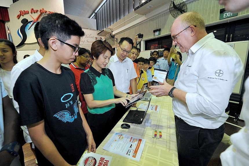 (From left) Jurong Secondary student Dario Ng, South West District Mayor Low Yen Ling and Jurong GRC grassroots organisations' adviser, Dr Tan Wu Meng, trying out a quiz on dengue, with guidance from Mr Jason Nash (right), innovation manager and vect