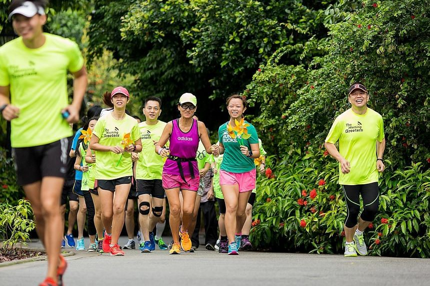 Members of The Morning Greeters on their run as they handed paper windmill daisies out to people at the Singapore Botanic Gardens yesterday morning, in celebration of Kindness Day SG. They were joined by actor Zhang Zhen Huan, national para-athlete B