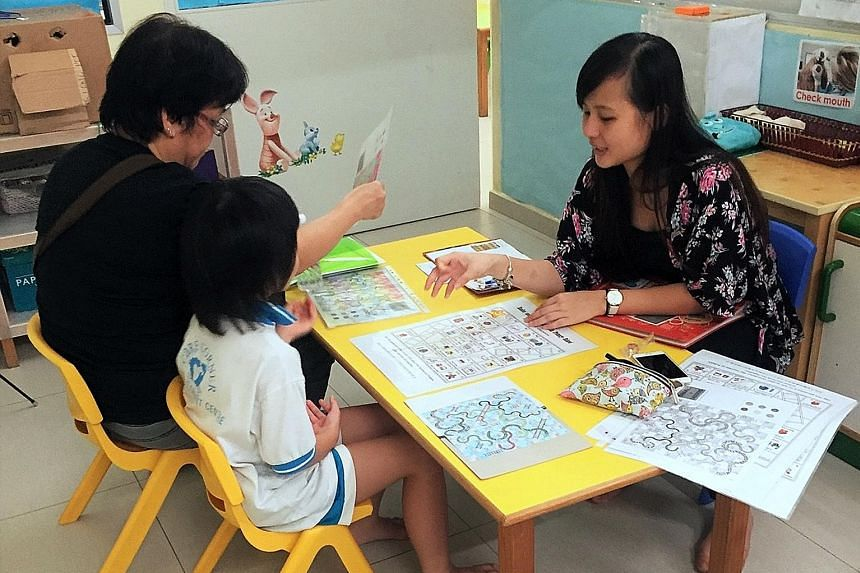 A volunteer helping a parent and child at a Transition to P1 playshop organised under the Circle of Care scheme, which has led to higher rates of school attendance and gains in learning for at-risk children at the two centres in Leng Kee and Admiralt