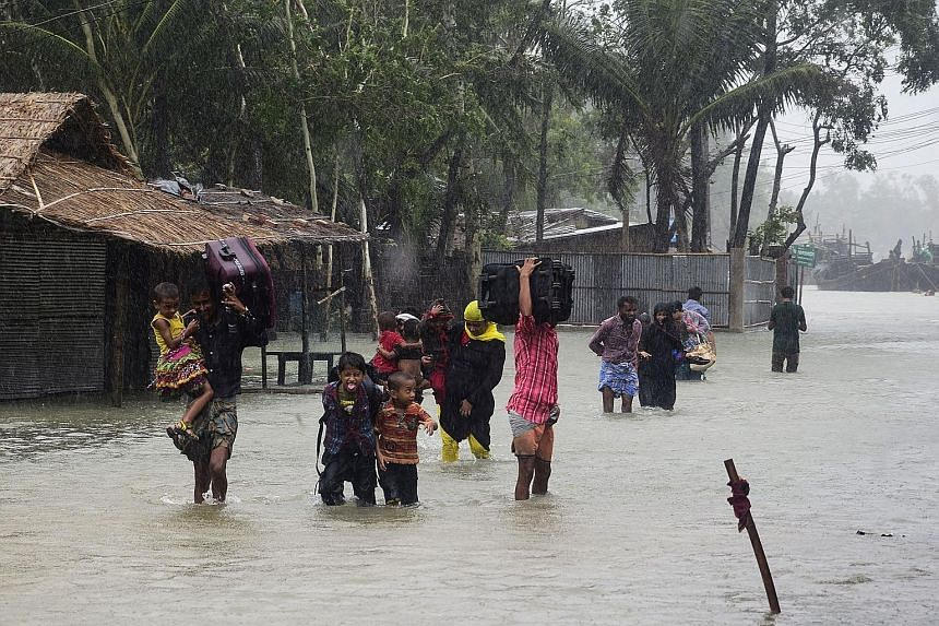 Debris of damaged shops at Patenga Beach in Chittagong after the cyclone hit. About half of those who died were from the Chittagong region which bore the brunt of the storm. Villagers making their way to shelter as Cyclone Roanu approached last Satur