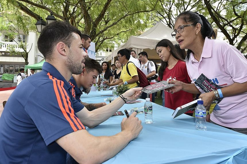 Valencia players signing autographs at UN Women's campaign for foreign domestic workers at Chijmes. This was the Spanish club's final stop during their five-day visit to Singapore.