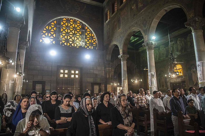 Relatives and friends of the EgyptAir crash victims attending a mourning ceremony yesterday at the Saint Peter and Saint Paul Coptic Orthodox Church in Cairo's Abbasiya district.