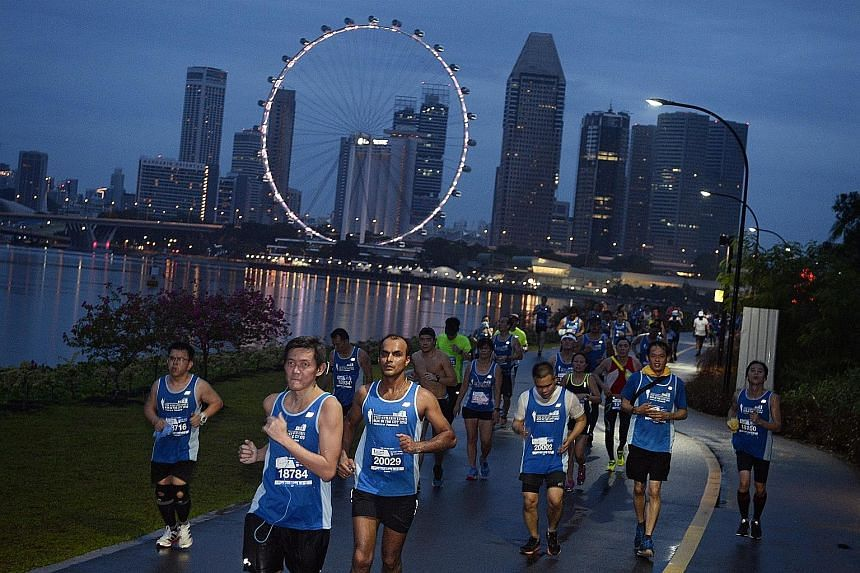 ST Run participants running along Gardens by the Bay East early yesterday morning. The ground may have been wet because of the rain, but their spirits were not dampened. Racegoers later enjoyed themselves at the post-race carnival at the F1 Pit Build