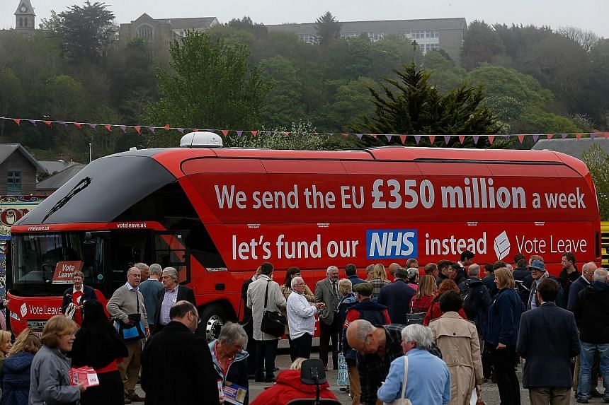 "Supporters of the ""Leave"" camp gathering around a campaign bus in Truro earlier this month. One economist has said that where Singapore is concerned, trade and investment flows would not change with Brexit as British goods do not get a preferential t"