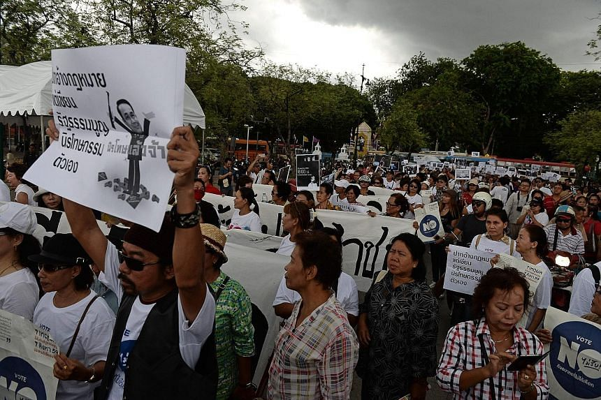 Anti-junta demonstrators marching against military rule at Bangkok's Democracy Monument yesterday on the second anniversary of Thailand's military coup. A poll has found that 43 per cent of Thais felt no happier than before the coup, and 18 per cent