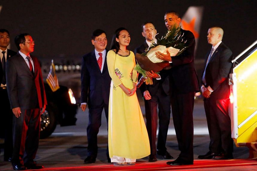 US President Barack Obama receives flowers as he arrives at Noibai International Airport in Hanoi on May 22, 2016.