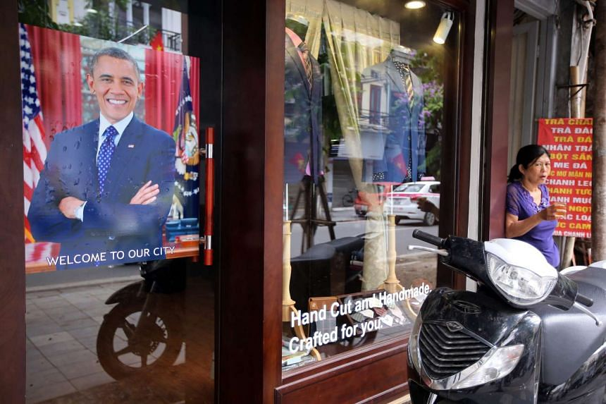 A woman stands next to a poster showing US President Barack Obama outside a tailor shop in Hanoi on May 22,  2016.