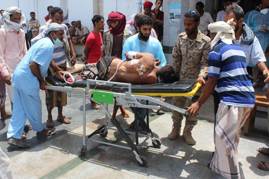 An injured Yemeni man is carried on a stretcher at a hospital following twin bombings that targeted Yemeni forces in Aden, on May 23, 2016.