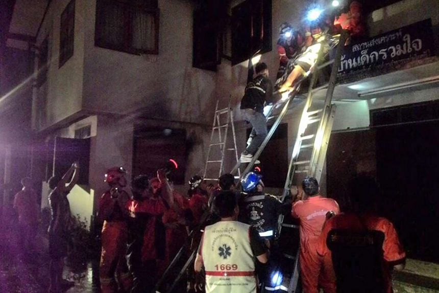 Thai firefighters and rescue workers remove an injured Thai student (top) after a fire broke out at a school dormitory in Chiang Rai province, northern Thailand.