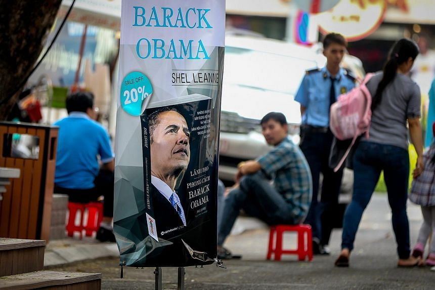 People sitting near an advertisement for a book about US President Barack Obama outside a book store in Ho Chi Minh City, Vietnam, on May 22, 2016.