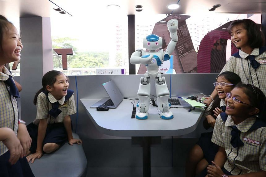Students from Wellington Primary School burst into laughter as a robot dances to Gangnam Style in the Lab on Wheels, a retrofitted bus filled with computers and robotics.