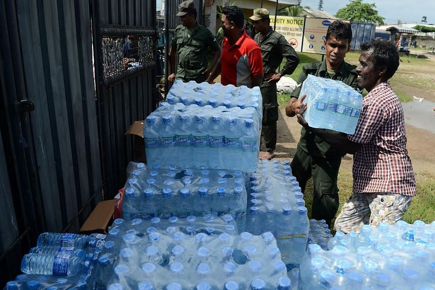 Sri Lankan army personnel distribute bottles of water to a flood victim in Kelaniya, on the outskirts of Colombo on May 22, 2016.