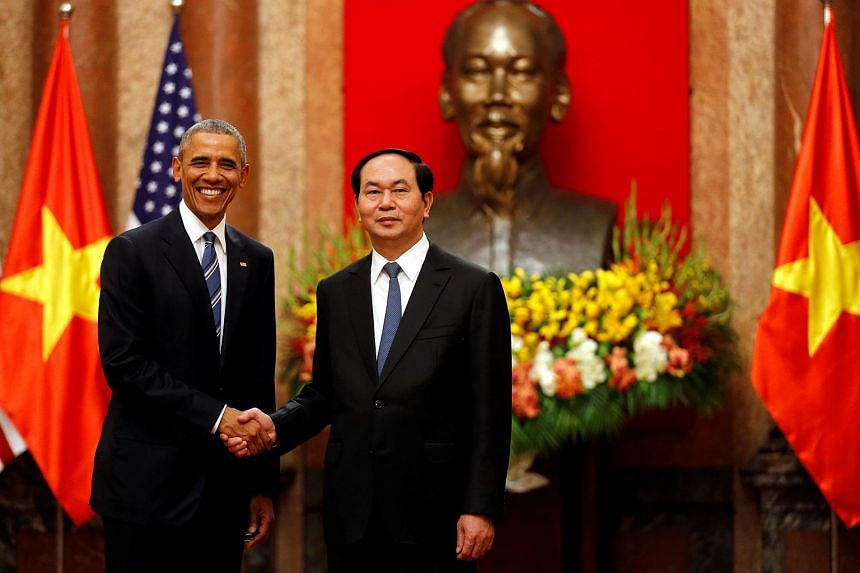US President Barack Obama shakes hands with Vietnam's President Tran Dai Quang after an arrival ceremony at the presidential palace in Hanoi.