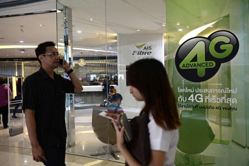 People use their mobile phones in front of 4G advertising in a shopping mall in Bangkok. on March 21, 2016.