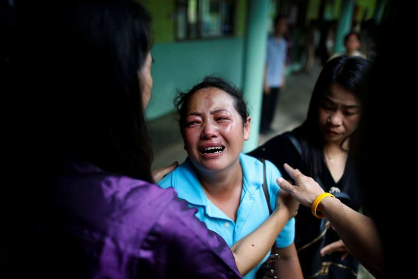 Malawian Saw-wa, 33, who lost her daughter, cries near a burnt building at the Pitakkiat Wittaya School in Chiang Rai, Thailand, on May 23, 2016.