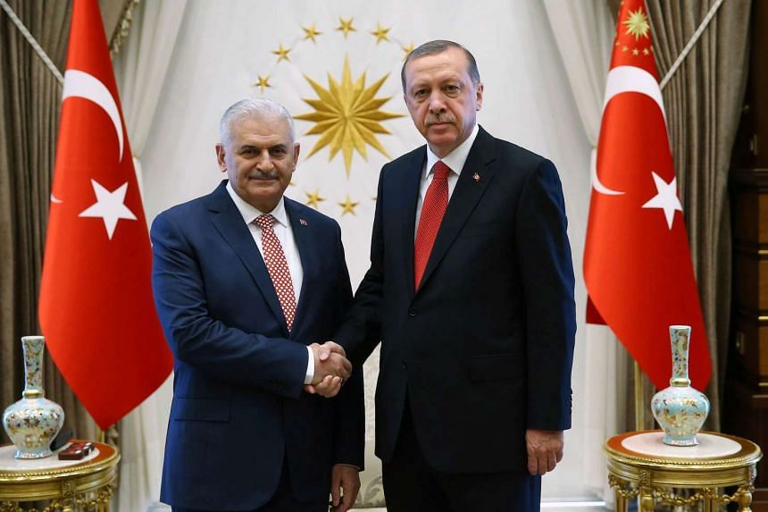 Turkey's new Prime Minister Binali Yildirim (left) shakes hands with President Recep Tayyip Erdogan in Ankara, on May 24, 2016.