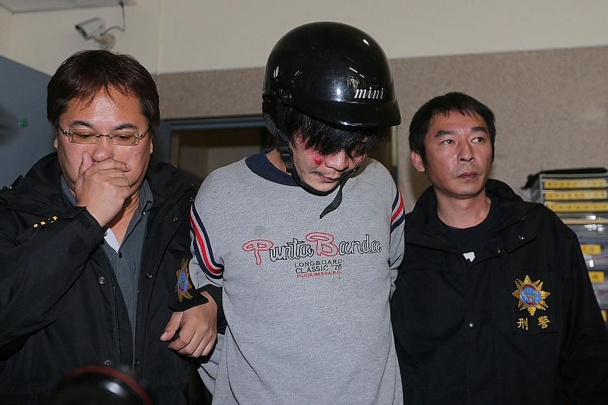 """Wang (centre) is accused of beheading a four-year-old girl in March, in the presence of her mother, an act described as """"extremely cold-blooded"""" by Taiwanese prosecutors."""