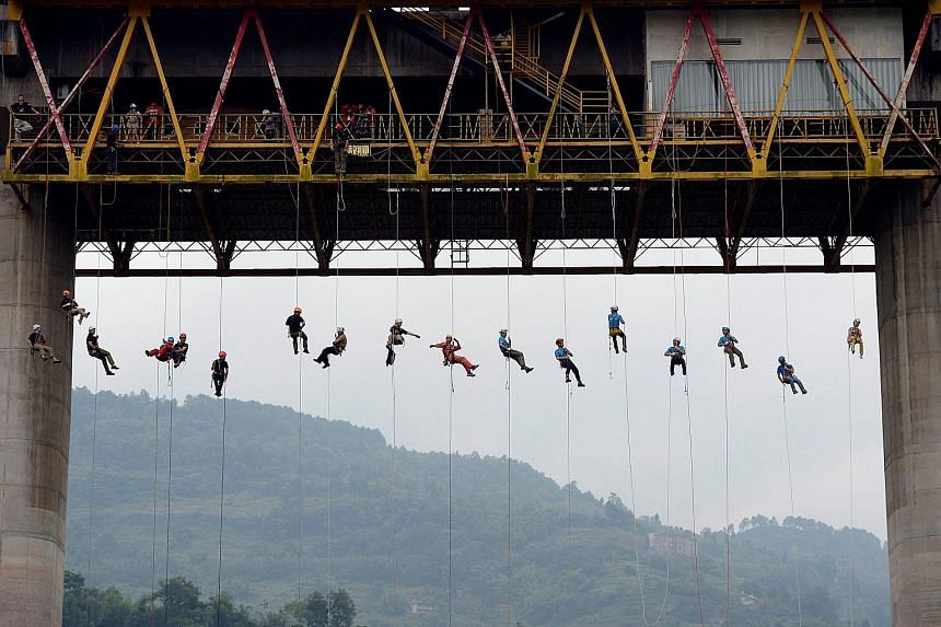 Participants hanging from a bridge 40m above the ground during a drill at a scenic spot in Fuling district, in China's Chongqing municipality, on Sunday. More than 30 enthusiasts were selected to take part in the drill, which was held by the local fi