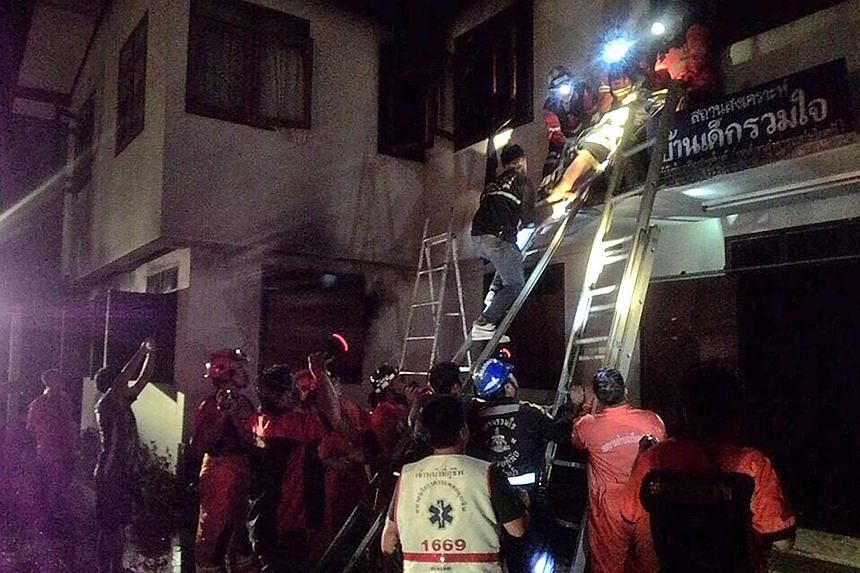 Firefighters and rescue workers saving an injured pupil after a fire broke out late on Sunday in the dormitory of a boarding school in Thailand's northern Chiang Rai province.