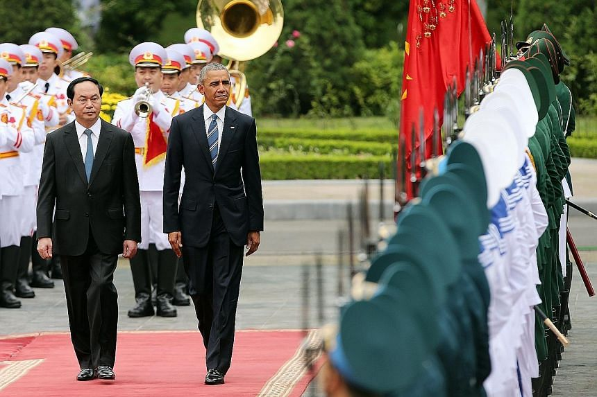 "President Obama reviewing a guard of honour with President Quang at the Presidential Palace in Hanoi yesterday. Mr Quang said the lifting of the US ban on sales of lethal weapons to Vietnam ""is clear proof that both countries have completely normalis"