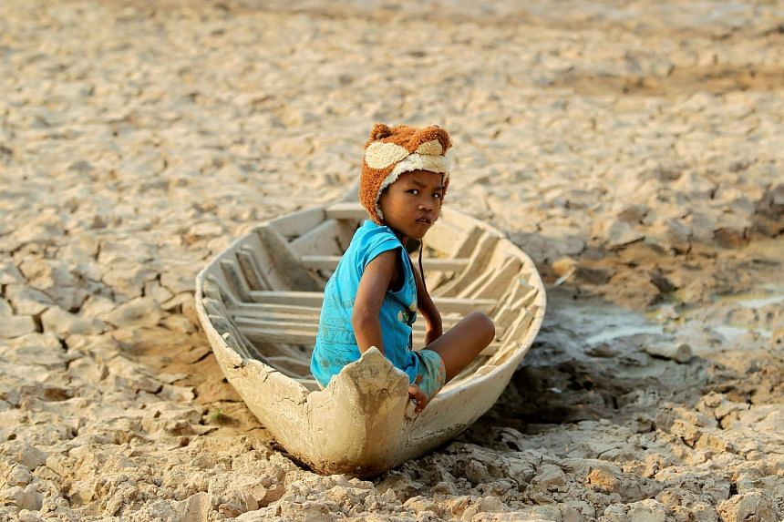 A girl sits on her boat at a Bak Angrout dried up pond at the drought-hit Kandal province in Cambodia.