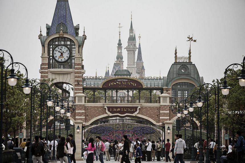 Visitors walk past a gate at Walt Disney Co.'s Disneyland Resort in Shanghai, China.