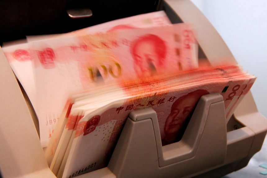 Chinese 100 yuan banknotes are seen in a counting machine while a clerk counts them at a branch of a commercial bank in Beijing, China on March 30.