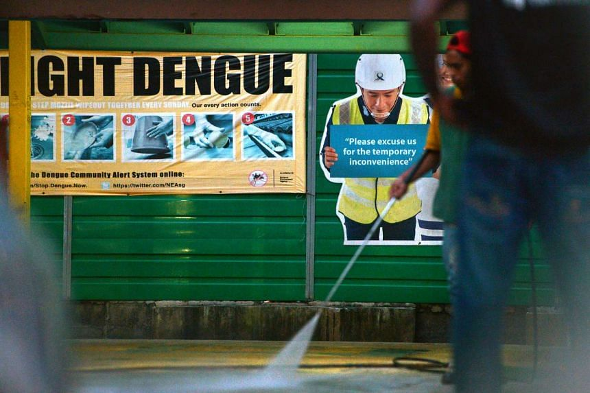 "A ""Fight Dengue"" poster on a hoarding in front of a construction site along Tampines Avenue 4."