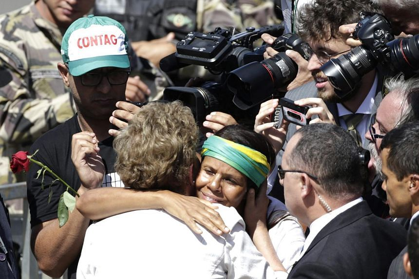 Brazilian President Dilma Rousseff (centre) greets supporters outside the Planalto Palace, in Brasilia, Brazil on May 12.