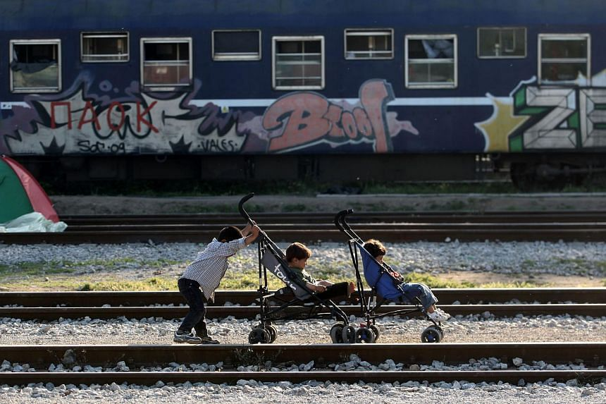 Children play next to railway tracks at the refugee and migrant makeshift camp on the Greek-Macedonia border near the village of Idomeni on May 23.