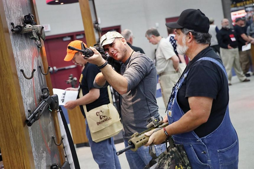 Gun enthusiasts look over E O Tech optics at the National Rifle Association Annual Meetings & Exhibits at the Kentucky Exposition Center on May 21, 2016 in Kentucky, US.