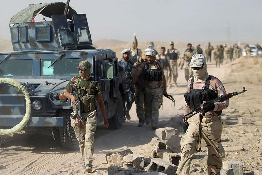 Iraqi pro-government forces gather as they advance towards the city of Fallujah.