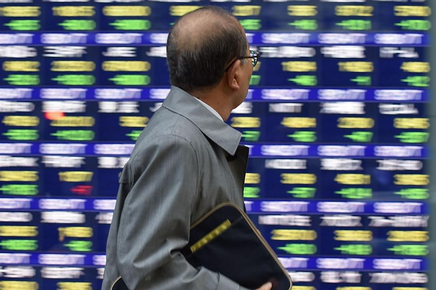 A pedestrian looks at a quotation board flashing the Nikkei key index from the Tokyo Stock Exchange.