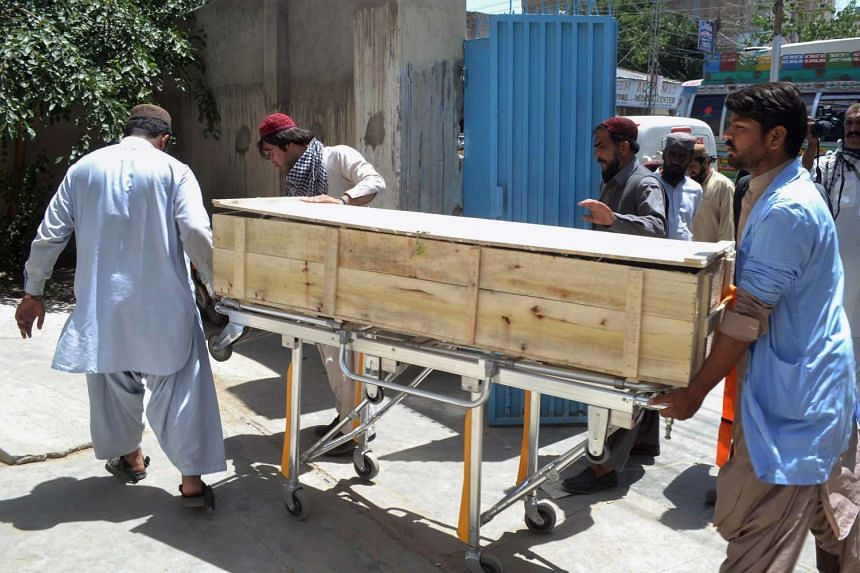 Pakistani security officials and hospital staff move a dead body into a morgue on May 22, 2016, following a drone strike that targeted Taleban chief Mullah Akhtar Mansour.